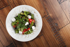 Greek salad. On a white plate. top view. wooden background Royalty Free Stock Image