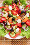 Greek salad on a white plate. Vegetable salad with cheese on white plate Stock Photos