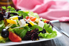Greek salad. On white plate on wooden background closeup Stock Photos