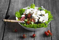 Greek salad wit tomato, cheese and olives. On wooden background stock photos