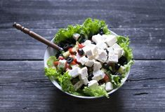 Greek salad wit tomato, cheese and olives. On old wood royalty free stock photo