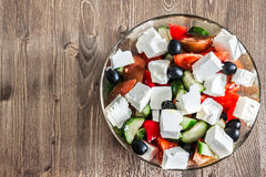 Greek Salad on wooden background. Greek salad in bowl on wooden table with copy space stock image