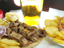 Greek Souvlaki. With gyros white cheese, olives, potatoes and beer stock photo