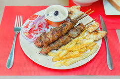 Greek souvlaki with fries and cream cheese on a table in a restaurant. Barbecue, bread, closeup, cuisine, delicious, dinner, dish, fast, food, fresh, fried Royalty Free Stock Image