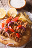 Greek souvlaki kebab with tomatoes and onions close-up. Vertical Royalty Free Stock Photo