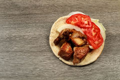 Greek souvlaki with pita bread and vegetables close-up on the table. Pork table Royalty Free Stock Images