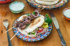 Greek souvlaki served in a traditional way, on pita bread with onion rings and lemon Royalty Free Stock Photo
