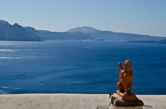 Greek statue in Santorini. Clay statue of a Greek sphinx with the head of a woman and body of a lion with the Aegean Sea and caldera of Santorini in the Royalty Free Stock Photos
