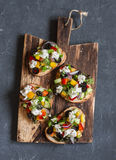 Greek style bruschetta on a wooden cutting board, on dark background, top view. Royalty Free Stock Images
