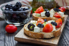 Greek style crostini with feta cheese, tomatoes, cucumber, olives, herbs Stock Photo
