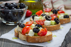 Greek style crostini with feta cheese, tomatoes, cucumber, olives, herbs Royalty Free Stock Photography