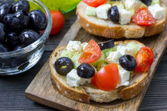 Greek style crostini with feta cheese, tomatoes, cucumber, olives, herbs Stock Images