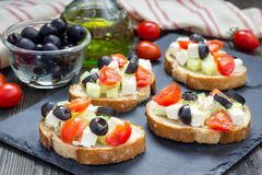 Greek style crostini with feta cheese, tomatoes, cucumber, olives, herbs Stock Photography