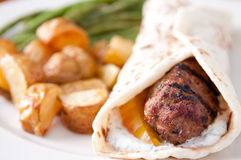 Greek style hamburger rolled in a flatbread Royalty Free Stock Images