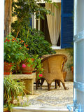Greek style patio. Plants and chairs on a comfortable patio or courtyard in Greece Stock Images