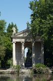 Greek style temple in Rome. Greek style temple with a statue of the god Aeklepios (Aesculapius) on an island in the pond at the garden of Villa Borghese, Rome Stock Image