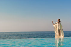 Greek style woman stand on infinity pool Stock Images