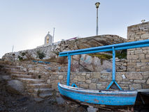 Greek styles and colours. A typical view of Mykonos and Greece - The colourful boat and the white cross with bells over the church stock photos