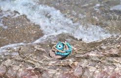 Greek summer bracelets with evil eye on beach Stock Image