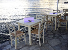 Greek tavern concept by the sea with wooden chairs Stock Photography