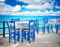 Greek tavern. Image of a greek outdoor restaurant with blue tables and chairs by the sea Stock Photos