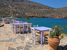 Greek tavern with pink and lilac tables and white chairs overloo Stock Photo