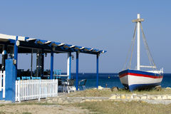 Greek tavern with sea view and boat Royalty Free Stock Photos