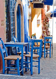 Greek taverna. Image of a greek outdoor restaurant with blue tables and chairs Stock Image
