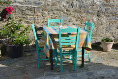 The Greek Taverna. Authentic Greek taverna furniture consisting of a wooden table with a square board, which is covered necessarily checkered tablecloth and stock images