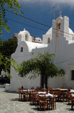 Greek taverna and church and monastery. Greek taverna dining next to beautiful church with monastery on mountain in background Folegandros Cyclades island Greece Stock Photo