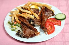 Greek taverna grilled lamb chops. Grilled lamb chops at a greek taverna, served with tomato, potato chips, vegetable rice, tomato and cucumber royalty free stock photography