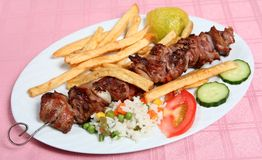 Greek taverna lamb souvlaki kebab. A lamb souvlaki, or kebab, on the skewer, served with french fried potato chips, rice and vegetables at a taverna royalty free stock photography