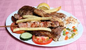 Greek taverna mixed grill. A Greek taverna's  mixed grill of souvlaki kebab skewer, lamb chops, belly pork chop, yoghourt, rice and potato chips with salad and Stock Photography
