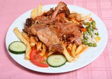 Greek taverna rabbit stifado. Traditional Greek rabbit stifado, or stew, at a taverna in Greece, served with french fries, rice and vegetables stock photos