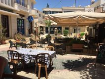 A Greek taverna square in the sun. Greek taverna in a town square Royalty Free Stock Image