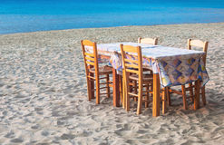Greek taverna table and chairs on sandy beach Royalty Free Stock Photography