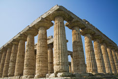 Greek temple. The temple of Hera, built around 550 BCE by Greek colonists, in Paestum, Italy. Low angle view against blue sky Royalty Free Stock Photography