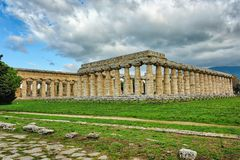 Greek temple in southern Italy on greenery under blue skies with stock image