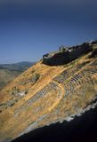 Greek theatre built into steep mountain slope Royalty Free Stock Photography