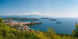 Greek town in a bay. Liner ship moored in a bay next to a traditional Greek town stock image