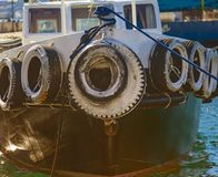 Greek Tug Boat Anchored in Marina. Small tug boat`s bow with protective car tires as fenders. Close-up Royalty Free Stock Photos