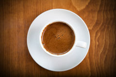 Greek turkish coffee served in a white cup. On wooden table, upper view Stock Images