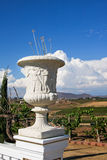 Greek Vase in a Vineyard. A white stone greek vase sitting on a wall with greek figures carved into the stone. There is rolling hills of a beautiful vineyard in Royalty Free Stock Photography