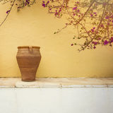 Greek village house detail. Vintage vase over wall background Stock Photo