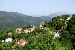 Greek Village Houses. Small houses, or cottages, in overgrown lush green foliage in Greek mountain village Stock Photo