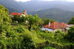 Greek Village Houses. A small house, or cottage, iand church in overgrown lush green foliage in Greek mountain village Stock Photo