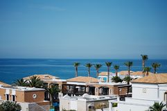 Greek village near the sea. Aldemar Cretan Village Resort. Beautiful, little, spectacular, greek buildings near the sea. Wide, clear sky, blue sea and line of Royalty Free Stock Image
