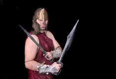 Greek warrior man. One strong thirties Greek warrior with swords in full costume over black Stock Photography