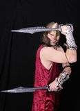 Greek warrior man. One strong thirties Greek warrior with swords in full costume over black Royalty Free Stock Photo