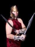 Greek warrior man. One strong thirties Greek warrior with swords in full costume over black Royalty Free Stock Image
